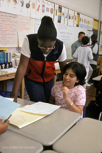 Oakland CA Elementary school girl admiring classmate's writing work in class