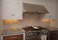 This custom kitchen features a handmade Tatami Radiance mosaic backsplash shown in polished Bardiglio, Horizon, Cashmere, Carrara, and Calacatta Tia from New Ravenna.<br />