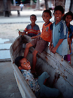 May 25th 2004_ Com, Timor-Leste_ A group of children play in an old dugout fishing boat in the town of Com.  Com is located in Lautem district and is known for it's beautiful beaches and great diving.  Photograph by Daniel J. Groshong/Tayo Photo Group