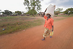 Asanta Jantana walks along a road in Kotobi, South Sudan, carrying some of the food and non-food items she received during a distribution of aid to displaced families. She is one of thousands who were displaced by political violence that broke out in December 2013 and quickly fractured regions of the young nation along ethnic and tribal lines. Jantana fled Juba with her seven children for this village, where she moved in with a brother. Yet she hasn't had enough food for her whole family, so she sent four of her children to live with another relative. She hasn't heard from her husband, a soldier, since the fighting began. Finn Church Aid, a member of the ACT Alliance, provided materials for this aid distribution.