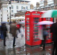 Red telephone boxes, designed by Sir Giles Gilbert Scott (1880 - 1960), preserved as a tourist attraction near Covent Garden, London, UK, beneath a rainy day. Picture by Manuel Cohen