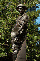 "This statue on Charlotte's Trade and Tryon streets Square is one of four standing on each corner of the intersection. The sculptures were created by artist Raymond Kaskey and are titled ""Transportation,"" ""Future,"" ""Commerce,"" and ""Industry."" This statue, Commerce, is symbolized by a gold miner spilling money on the head of a banker."