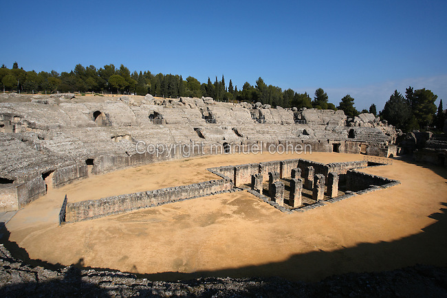 High angle view of Amphitheatre, Italica, Seville, Spain, pictured on December 28, 2006, in the afternoon. The Amphitheatre was built during Hadrian's reign and was the third largest in the Roman Empire, with a capacity of 25,000 in three tiers of seating. The cross shaped pit in the centre was for restraining wild animals. Italica was founded by Scipio Africanus in 206 BC as a centre for soldiers wounded in the Battle of Ilipa, a defeat for Carthage during the Punic Wars, and became a military outpost. The name signifies that the original settlers were from an Italian regiment. It was one of the first cities in Roman Hispania and was the birthplace of two Roman Emperors: Trajan (53-117 AD) and Hadrian (76-138 AD). The city declined after the fall of the Roman Empire. Picture by Manuel Cohen.