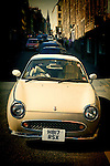 Retro Nissan Figaro car parked on street in urbanenvironment