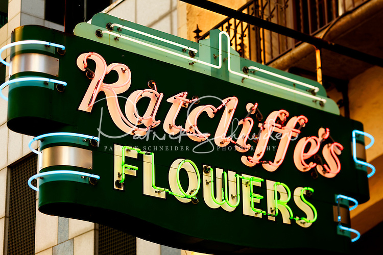 The neon Ratcliffe's Flower sign still hangs outside the Mediterranean Revival Style Ratcliffe Flowers building, a Charlotte landmark located in downtown Charlotte, NC. Built in the 1920s, the building that originally housed a florist shop became a restaurant (Carpe Diem) in the 1990s. When the building was transformed into the midrise Ratcliffe Condos in 2002, the shop was moved during construction and then replaced in its original position. The residential and retail building was then constructed around the original Ratcliffe's shop. Today, the former flower shop is home to Ratcliffe On The Green, a restaurant of French-influence cuisine. The Ratcliffe Condos sit on The Green, an uptown Charlotte Center City project that includes an underground parking deck with a passive park on top. The Green park includes fountains, landscaped walkways, motion-activated stone walls, chess boards built into stone tables and riddles on the ground.