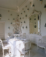 Chinese vases are displayed on Rococo consoles mounted on the walls of this all-white dining room