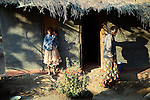 MPHANDULA, MALAWI - AUGUST 21: Ethel Dailesi, age 44, walks out of her house as her daughter Rebecca Masawo, age 10, stands nearby on August 21, 2006 in Mphandula village, about 30 miles outside Lilongwe, Malawi. Ethel was diagnosed with HIV/Aids in 2004 and has been on antiretroviral drugs since December 2005. She has just taken her medicine. She is often sick and her two daughters take care of her. Her children cook and clean for her. The girls attend a school nearby but they usually stay home when their mother is too sick. Mphandula is a poor village in Malawi, without electricity or clean water. Nobody owns a car or a mobile phone. Most people live on farming. About 7000 people reside in the village and the chief estimates that there are about five-hundred orphans. Many have been affected by HIV/Aids and many of the children are orphaned. A foundation started by Madonna has decided to build an orphan center in the village through Consol Homes, a Malawi based organization. Raising Malawi is investing about 3 million dollars in the project and Madonna is scheduled to visit the village in October 2006. Malawi is a small landlocked country in Southern Africa without any natural resources. Many people are affected by the Aids epidemic. Malawi is one of the poorest countries in the world and has about 1 million orphaned children. (Photo by Per-Anders Pettersson)