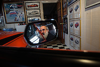 Reinholds, Pennsylvania, February 10, 2015 - A portrait of Brian Moyer in the mirror of his 1970 AMi (Australian Motor Industries) Gremlin in one of his garages. This one-of-a-kind car is the only one produced by AMI - used to sell the Gremlin to the Australian market it never took off due, Moyer says, to the limited space of the second row. He is still in the process of fully restoring it. Starting in 1960, AMI began assembling a braod range of AMC cars in the hopes of avoiding  high tarriff, all with right hand drive and the Rambler logo, even though the Rambler logo had long since been dropped in the US Market. <br /> <br /> Moyer owns 16 AMC Gremlins. The Gremlin was introduced on April Fools Day (April 1) in 1970 featuring a shortened Hornet body with a Kammback tail and was manufactured in the US via AMC and in Mexico via AMC's subsidiary VAM. It's lifecycle ended in 1978 when it was replaced by the AMC Spirit. Moyer became interested as a kid when he saw the early Gremlin commercials in 1970. His first car was a Gremlin and he has never not owned one. Today he has arguably the most unique collection of Gremlins in the world, including several that are one-of-a kind models. <br /> <br /> CREDIT: Daryl Peveto for The Wall Street Journal<br /> Photo Assignment ID: 36892 <br /> Slug: MYRIDE_Gremlin