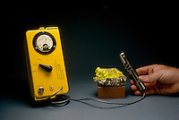 GEIGER COUNTER AND URANIUM MINERAL AUTUNITE.Uranium Ore Radioactivity Measured.A gas mixture (either argon and ethanol or neon and bromine) inside the Geiger counter cylinder, with high potential difference between central wire and walls of cylinder. Radiation ionizes the gas, resulting in one click per nuclear disintegration unit.