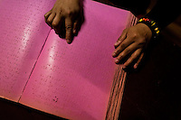 A blind girl reads a book written in Braille at Unión Nacional de Ciegos del Perú, a social club for the visually impaired in Lima, Peru, 6 April 2013. Unión Nacional de Ciegos del Perú, one of the first societies for disabled in Latin America, was established in 1931 to provide a daily service for blind and partially sighted people from the capital city. The range of activities includes reading books in a large Braille library, playing chess or using a computer adapted for visually impaired individuals. As the majority of the blind does not have a regular job, the UNCP club offers them an opportunity to learn and lately, to provide massages to the club visitors and thus generate some income.