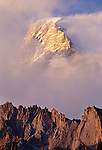 The vertical rise of the ridges is echoed by the lift of the massive peak of Mount Ultar out of the clouds, Himalaya Range, Pakistan.