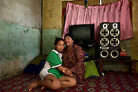 Indonesia - Bangka Island - Batako - Malasari Amirudin, 33 years old sitting next to her 15 year old daughter Novi Akher are portrayed in the room where they live sharing an apartement with 5 other miners. Amirudin has mined since she was ten, collecting tin scraps falling from the washing lines. Recently, she was joined by her daughter, who had just come from Pangkalpinang, the capital of Bangka. In a day, they can gain around 20 USD by collecting 3 kg of low concentrate tin.