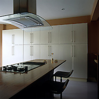 A wall of cupboards in the contemporary kitchen provides ample storage