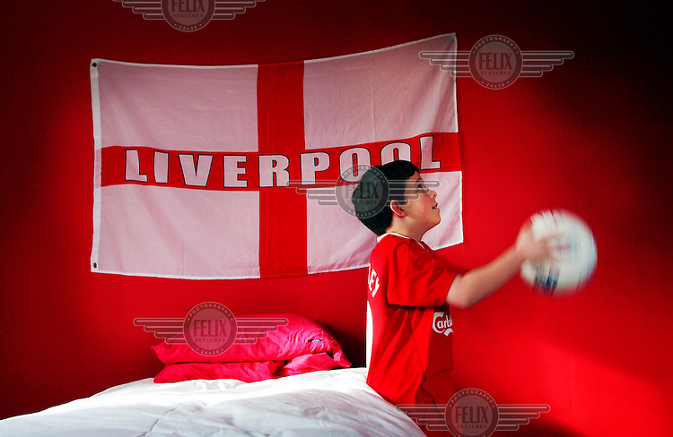 Ten-year-old Oliver Dewdney plays with a football below a Liverpool F.C. flag that is hanging in his bedroom.