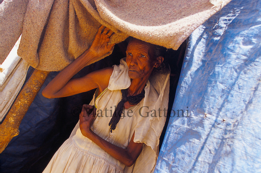 Eritrea - Debub- Old woman suffering from sevre malnutrition in an IDP camp. As a result of 30 years of war for independence against Ethiopia (from 1961 to 1991) and another 3 years from 1997 to 2000, there are 50,000 Eritreans currently living in internally displaced (IDP) camps throughout the country. These IDPs have fled three times in the last 10 years, each time because of renewed military conflict. They lived in relatives' homes when lucky enough, but mostly, the fled to the mountains, where they attempted to do what Eritreans do best, survive. Currently there is no Ethiopian occupation in Eritrea, but landmines prevent the IDPs from finally going home. .It is estimated that every Eritrean family lost two or three members to the war which makes the reality of the current emergency situation even more painful for Eritreans worldwide. Currently, the male population has been decreased dramatically, affecting the most fundamental socio-economic systems in the country. Among the refugee population, an overwhelming majority of families are female-headed, severely affecting agricultural production. For, IDPs in particular, 80% of households are female-headed..The unresolved border dispute with Ethiopia remains the most important drawback to Eritrea's socio-economic development, as national resources (human and material) continue to be prioritized for national defense. Eritrea is vulnerable to recurrent droughts and variable weather conditions with potentially negative effects on the 80 percent of the population that depend on agriculture and pastoralism as main sources of livelihood. The situation has been exacerbated by the unresolved border dispute, resulting in economic stagnation, lack of food security and increased susceptibility of the population to various ailments including communicable diseases and malnutrition..