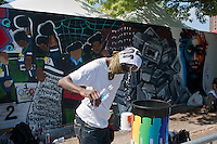 """A graffiti artist cools off at the AfroPunk Festival in Commodore Barry Park in Brooklyn in New York on Sunday, August 26, 2012. The festival in the neighborhood of Fort Greene bills itself as the """"other black experience"""" and blends the black punk and hardcore punk scenes. There is also a diverse aspect combining other minority groups, all dressed in their fashionable punk ensembles. (© Richard B. Levine)"""