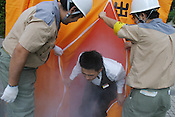 Members of the Japanese public undergo emergency/disaster training, including crouching below a table in an earthquake simulator, give mouth to mouth resucitation, and emerging from a smoke filled tunnel, in Nishi-Shinjuku, Tokyo, Japan