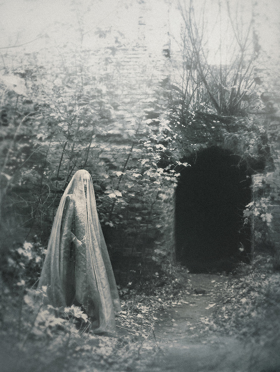 A ghostly figure in a veil, standing on a path to a mysterious entrance or a cave.