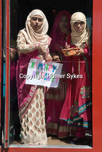 "Muslim women Brick Lane London wait for wedding guests to enter a resturant. The sign she holds reads ""No Money No Honey""' a tradition in Bengali wedding for the brides relatives to tease the groom into giving a small gift of money, a dowry, once thats done the ribbon is cut and he is allowed in."