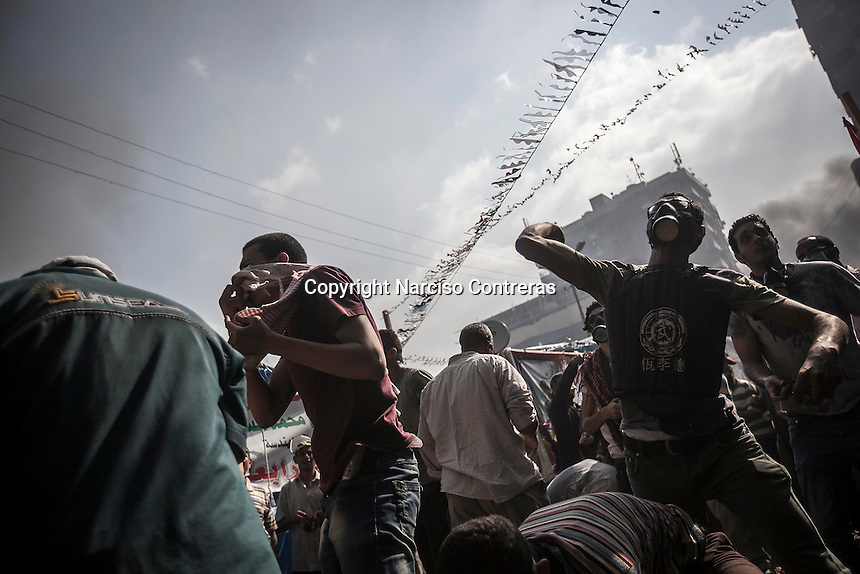 In this Wednesday, Aug. 14, 2013 photo, supporters of the ousted president Mohammed Morsi throw stones to the police during clashes with security forces in streets around Al-Raba'a Alawya mosque in the Nasr district of Cairo. (Photo/Narciso Contreras).
