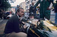 Formula 1: Engineer Colin Chapman talking to driver Graham Hill (twice world champion) in Lotus before Monaco Grand Prix, 1967.