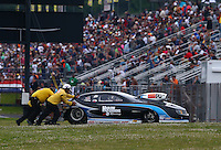 May 17, 2014; Commerce, GA, USA; Members of the Safety Safari push the NHRA pro stock car of Chris McGaha off the track during qualifying for the Southern Nationals at Atlanta Dragway. Mandatory Credit: Mark J. Rebilas-USA TODAY Sports