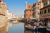 Bridge over canal in Chioggia, Italy. Typical Italian houses and gondolas.