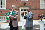 Athens Mayor Paul Wiehl (Left) opens a gift from Ohio University President Roderick McDavis at a ceremony for the opening of Bobcat Lane. Photo by Ben Siegel