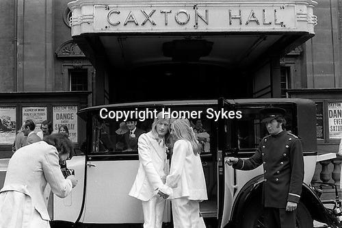 Caxton Hall, Westminster London. Londons main register office untill 1979. White wedding, his and her uni sex clothes, she is wearing a trouser suit. rather than a wedding dress, very fashionable at that time. 1970s London ..He is Michael Stephens, I think a well know hairdresser of the time. ..