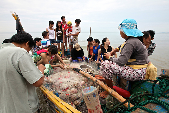 People gather around a fishing boat to see the morning's catch on the beach in Mui Ne, Vietnam. Nov. 20, 2011.