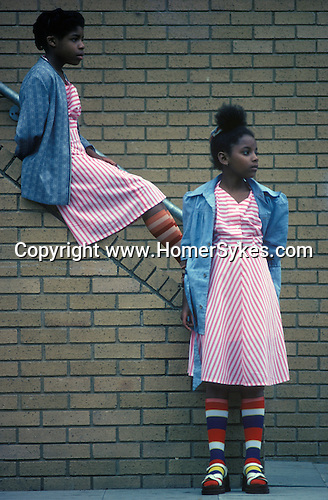 Young black twin girls, wearing same pink stripped dresses. Black community Notting Hill west London 1970s England UK