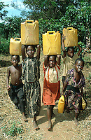 Uganda. Kayunga district. Nnongo. A group of young children carry on the heads or in their hands yellow jerrycans full of water fetched at a well.© 2004 Didier Ruef