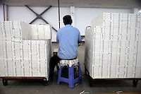 "An Amity Printing Company employee trims the pages of newly-bound Bibles in the Amity Printing Company's new printing facility in Nanjing, China....On May 18, 2008, the Amity Printing Company in Nanjing, Jiangsu Province, China, inaugurated its new printing facility in southern Nanjing.  The facility doubles the printing capacity of the company, now up to 12 million Bibles produced in a year, making Amity Printing Company the largest producer of Bibles in the world.  The company, in cooperation with the international organization the United Bible Societies, produces Bibles for both domestic Chinese use and international distribution.  The company's Bibles are printed in Chinese and many other languages.  Within China, the Bibles are distributed both to registered and unregistered Christians who worship in illegal ""house churches."""