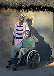 Nhaume Makavire and her husband Henry Gwese pose on their farm in Charumengwe, Zimbabwe. Gwese's legs were paralyzed by cerebral malaria, yet he and his wife continue farming. He uses an appropriately designed and fitted wheelchair provided by the Jairos Jiri Association with support from CBM-US.