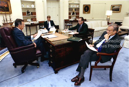 Washington, D.C. - August 29, 1990 -- United States President George H.W. Bush, left, meets with (left to right) Vice President Dan Quayle,  Office of Management and Budget (OMB) Director Dick Darman, and Secretary of the Treasury Nicholas Brady regarding budget matters in the Oval Office at the White House in Washington, DC on August 29, 1990..Credit: White House via CNP