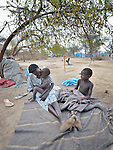 Adut Nyang and her children Muoi Wol, 3, and Akuk Wol, 6, sit under a tree in an internally displaced persons camp in Manangui, South Sudan. Families started arriving here shortly after fighting broke out in December 2013, and new families continued to arrive in March 2014 as fighting continued. Many are living in the open and under trees. The ACT Alliance is providing the displaced families and the host communities affected by their presence with a variety of support.