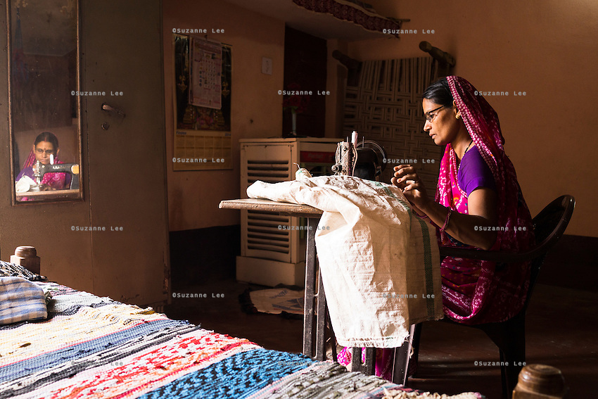 A fairtrade cotton farmer's wife, Lalita Jat, 40, mends a cotton collection sack in her home in Maheshwar, Khargone, Madhya Pradesh, India on 13 November 2014. Lalita had attended the sewing course started by the Fairtrade cotton farmers using the Fairtrade Premium and she is now able to save money for her family by making clothes and mending cotton collecting sacks. Photo by Suzanne Lee for Fairtrade
