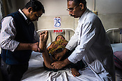 Dr. Mathew Varghese and his assistant doctor inspect the leg of their patient, 21 year old Rani at the Polio Ward of the St. Stephen's Hospital in Delhi, India. Dr. Mathew Varghese is the polio specialist who is providing path breaking technology and making polio patients walk, sometimes first time in their lives.
