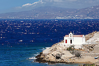 A small white chapel on a rocky coast of Chora in Mykonos, Greece