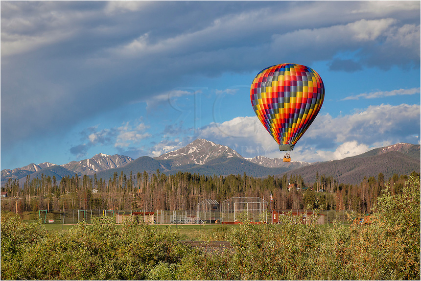 Over the Colorado Rockies, a hot air balloon floats across the morning sky. This image of the Rockies and a balloon comes from Grand County - Fraser, Colorado. The balloons usually lift off each morning at 6:30am. It is quite a nice site when the weather is calm.