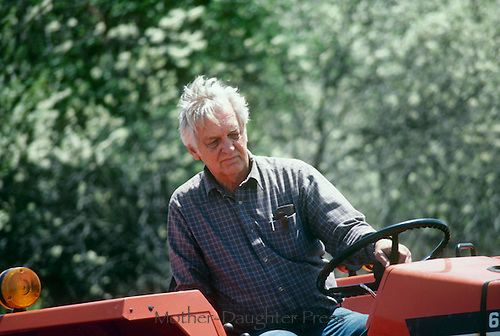 Older man, 75 years old, driving machine for hauling or mowing on summer day