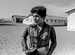 June 1981-Hot Camp-This Labor camp was near Patterson, California.  The scene was very bleak with no vegetation around the buildings and when you add the 100 plus degree temperature it seem to force the occupants to seek shade near the building.  Bee reporter Juan Esparza Loera had no trouble get everybody to talk.  <br /> Photo by Al Golub/Modesto Bee