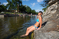 Sexy woman in bikini with sunglasses sunbathes lying on the limestone cliffs in the wading area at Barton Springs Pool, Austin, Texas.