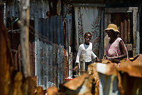 A Haitian woman leaves a shack in the slum of Cité Soleil, Port-au-Prince, Haiti, 11 July 2008. Cité Soleil is considered one of the worst slums in the Americas, most of its 300.000 residents live in extreme poverty. Children and single mothers predominate in the population. Social and living conditions in the slum are a human tragedy. There is no running water, no sewers and no electricity. Public services virtually do not exist - there are no stores, no hospitals or schools, no urban infrastructure. In spite of this fact, a rent must be payed even in all shacks made from rusty metal sheets. Infectious diseases are widely spread as garbage disposal does not exist in Cité Soleil. Violence is common, armed gangs operate throughout the slum.