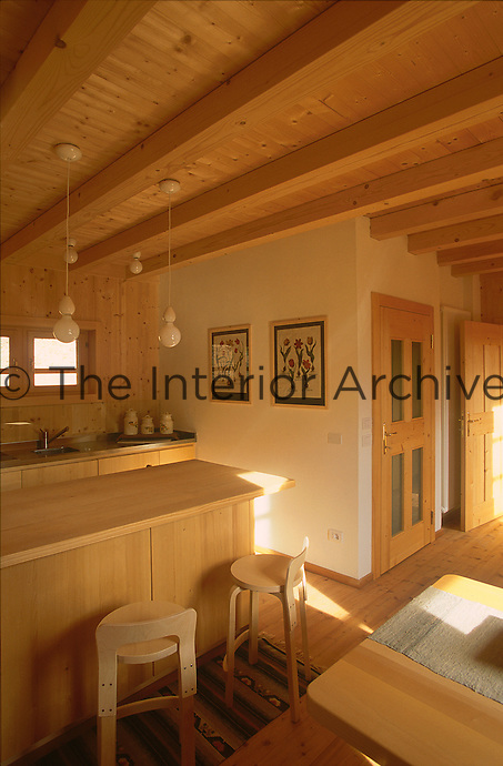The kitchen in the open plan living area is separated by a free-standing unit built in the same pine as the house