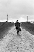 cowboy coming home carrying a suitcase and lasso on a dirt road in New Mexico