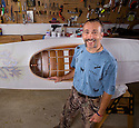 PE00009-00.....WASHINGTON - Phil Russel with one of his hand built skin kayaks with a hand painted map of the Pudget Sound on the front deck.