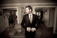 Adrian buttons his suit jacket after getting ready at his home in Bothell, WA for his wedding at the First Romanian Pentacostal Church. (Photo by Andy Rogers/Red Box Pictures)