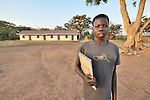A Southern Sudanese girl stands in front of her community's new school in the Southern Sudan village of Yondoru. Families here are rebuilding their lives after returning from refuge in Uganda in 2006 following the 2005 Comprehensive Peace Agreement between the north and south. For months students have held class under trees and in threadbare tents provided by UNICEF. Now they can meet in a new school provided by the United Methodist Committee on Relief (UMCOR). NOTE: In July 2011, Southern Sudan became the independent country of South Sudan