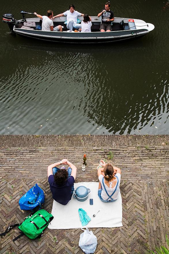 Nederland, Utrecht, 20 juli  2014<br /> Picknicken langs de Oudegracht in het centrum van Utrecht. Op een kleedje langs de kant van het water zitten en kijken naar voorbij komende bootjes is een uitstekend tijdverdrijf op een zomerse dag. <br /> Foto (c) Michiel Wijnbergh
